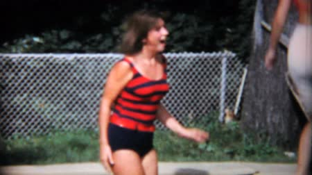 jimnastik : Teenage girls have fun jumping on an in ground trampoline in the back yard in the summer of 1967.