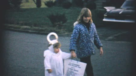 roliço : Kids get candy while trick or treating at Halloween dressed up in their costumes in the fall of 1967. Stock Footage