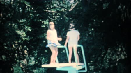 związek : Two girls play around on the diving board of the new backyard swimming pool in the summer of 1967. Wideo