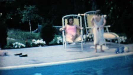 toalha : A pretty mother and daughter enjoy spending some time together by the family swimming pool in the summer of 1967. Vídeos