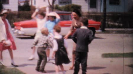 eğlence oyunları : A bunch of well dressed kids have fun playing and dancing with their Aunt in the driveway in 1962.