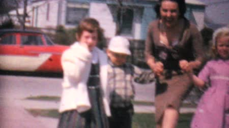 дичь : A bunch of well dressed kids have fun playing and dancing with their Aunt in the driveway in 1962.