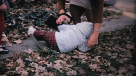 auxiliar : A cute little girl keeps falling on the sidewalk despite the help she receives from her older sisters and mother in the fall of 1961. Stock Footage