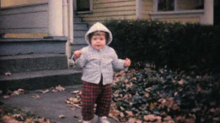 ona : A cute little girl keeps falling on the sidewalk as she learns to walk by herself in the fall of 1961.