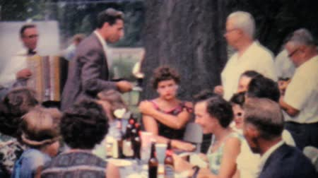 régi : People enjoy listening to an accordion player at a large family picnic in the summer of 1962.