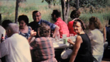 besinler : People enjoying a delicious meal at a large family picnic in the summer of 1962.