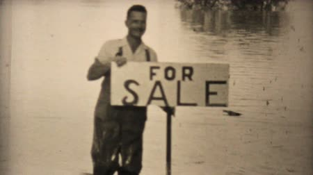 értékesítés : A man shows his sense of humor by holding up a for sale sign at his flooded home during the floods of 1948 in Dallas, Texas.