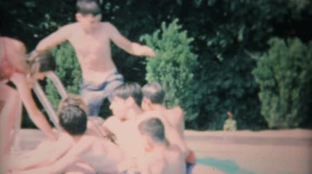 basen : Teenagers having a blast swimming and playing at a summer pool party in 1969. Wideo