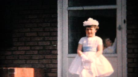 giydirmek : A cute little girl models her new Easter dress for the camera in front of her home in 1964. Stok Video