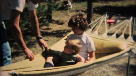 сбор винограда : Loving sisters enjoy spending time together swinging on the hammock in the summer of 1968.
