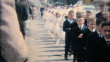 градация : Catholic school grads walk down the street in a processional in Pennsylvania.