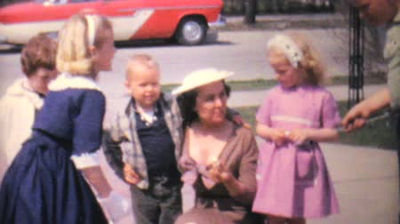 játék : A bunch of well dressed kids have fun playing and dancing with their Aunt in the driveway in 1962.