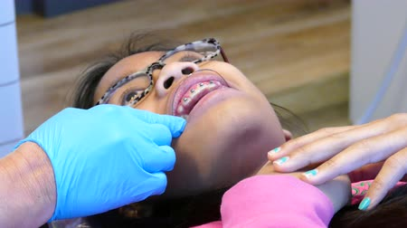 stomatologia : A young teenage Asian girl visits the orthodontist for her regular check up and adjustment appointment in Vancouver, BC.