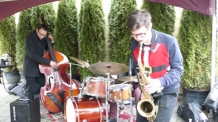 kalça : A cool jazz band trio plays Christmas carols over the holidays busking outside the shopping area for shoppers to enjoy!