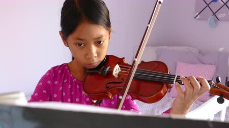 enstrüman : A cute little 9 year-old Asian girl diligently practices her violin in her bedroom.