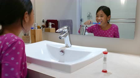 brushing : A cute little 9 year old Asian girl uses an egg timer to help her brush her teeth longer.
