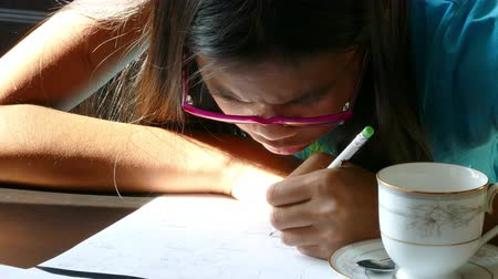 focalizada : A cute 13 year old Asian girl spends time drawing on the kitchen table while enjoying a sunbeam.