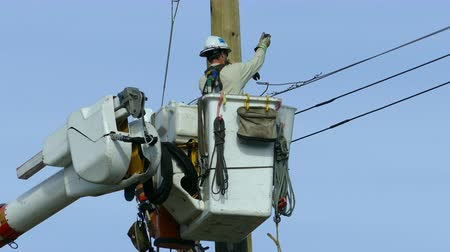 utilidade : VANCOUVER, BC, OCTOBER 2015: A hydro repair lineman in an safety jumpsuit and hard hat repairs a problem on the line in the city of Vancouver.
