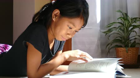 fegyelem : A cute little Asian girl enjoys reading her book and doing homework in her sunbeam in the afternoon.