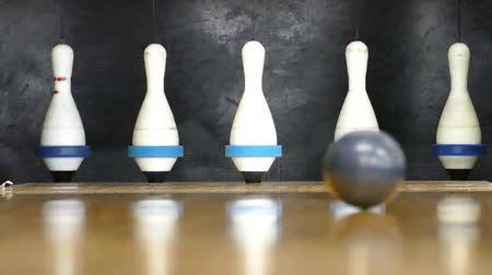 tigela : A close up shot of a bowling ball hitting the pins in a bowling alley.