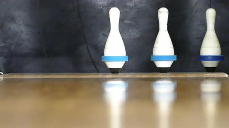 pino : A close up shot of a bowling ball hitting the pins in a bowling alley.