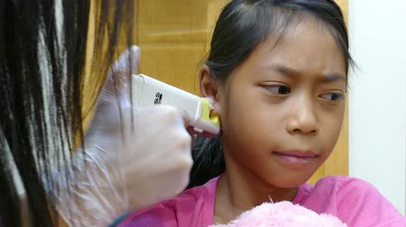 enstrüman : A cute little 9 year old Asian girl gets her ears pierced for the very first time.
