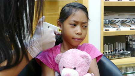 delici : A cute little 9 year old Asian girl gets her ears pierced for the very first time.