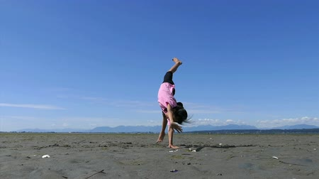 jimnastik : A cute little 9 year old Asian girl enjoys practicing her various gymnastic moves at the beach on a gorgeous sunny summer day.