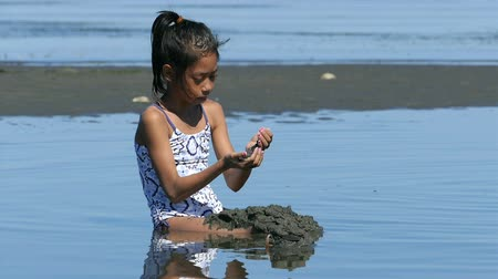 kopat : A cute little Asian girl enjoys spending time playing at the beach on a gorgeous sunny summer day.