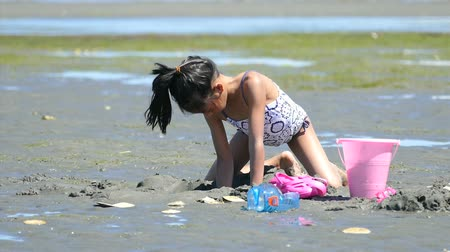 areia : A cute little Asian girl enjoys spending time playing at the beach on a gorgeous sunny summer day.
