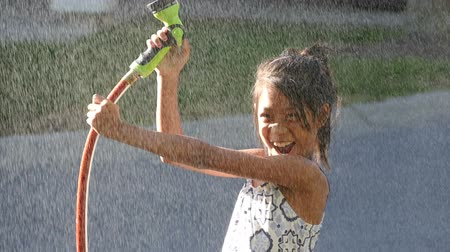 kanada : A cute little Asian girl enjoys spending time spraying herself with the garden hose on a gorgeous sunny summer day. Stok Video
