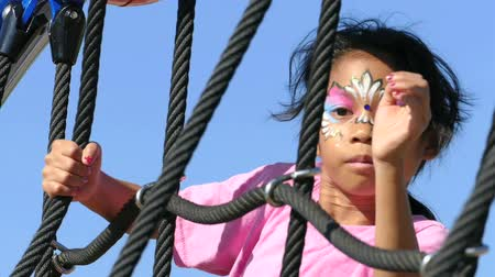 честолюбие : A cute little 9 year old Asian girl with her face painted enjoys the challenge of climbing on the playground structure. Стоковые видеозаписи