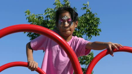 focalizada : A cute little 9 year old Asian girl with her face painted enjoys the challenge of climbing on the playground structure. Vídeos