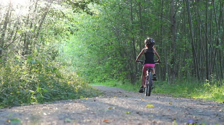 hrdý : A young Asian girl rides her new bike without training wheels for the first time down a pretty forest path.