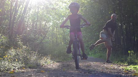 ailelerin : An excited dad helps her young Asian daughter ride her new bike without training wheels for the first time on the pretty forest path.