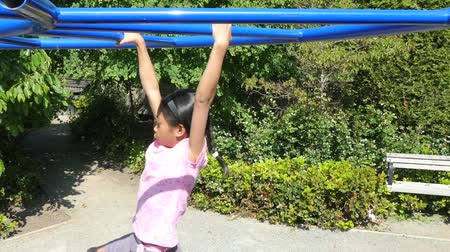 честолюбие : A cute little 9 year old Asian girl enjoys the challenge of climbing on the monkey bars at the playground.