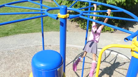 jimnastik : A cute little 9 year old Asian girl enjoys the challenge of climbing on the monkey bars at the playground.
