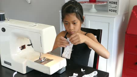 tajlandia : A cute Asian girl learning how to sew on her Moms sewing machine.
