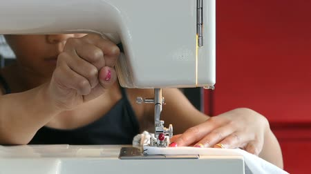 szycie : A cute Asian girl learning how to sew on her Moms sewing machine.