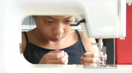 vyšívání : A cute Asian girl learning how to sew on her Moms sewing machine.
