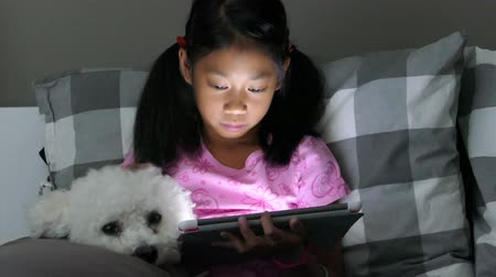 playing with a dog : A cute little Asian girl uses her tablet alone in her bedroom at night with her faithful puppy at her side.