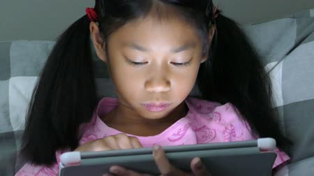 touchpad : A cute little Asian girl uses her tablet alone in her bedroom at night.