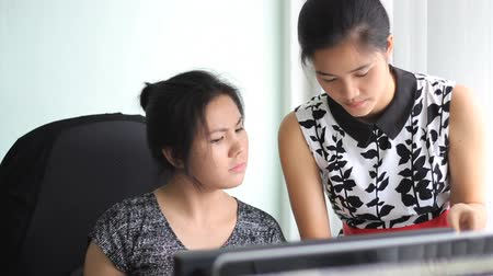 дружба : Two attractive Asian female young adult office workers collaborate together as they work in the office in Bangkok, Thailand.