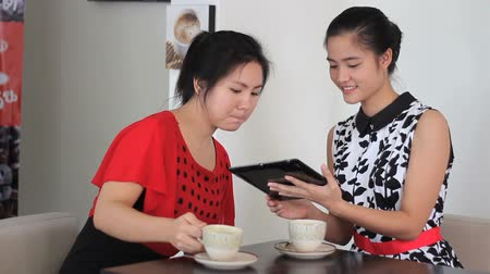 coffee time : Two attractive Asian young adult women enjoy spending time together and chatting over coffee in a cafe in Bangkok, Thailand.