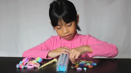 namiętność : A cute little 8 year old Asian girl has fun making colorful bracelets on her rainbow loom.