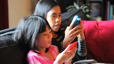touchpad : Two cute Asian sisters enjoy spending time together playing video games in the living room.