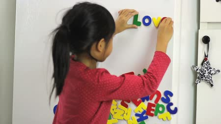 letras : A cute little seven year old Asian girl uses colorful fridge magnet letters to spell I Love Mom on the fridge.
