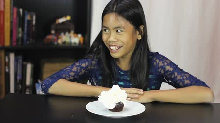 ostor : A cute twelve year old Asian girl is excited to have whip cream and sprinkles on her chocolate birthday cupcake. Stock mozgókép
