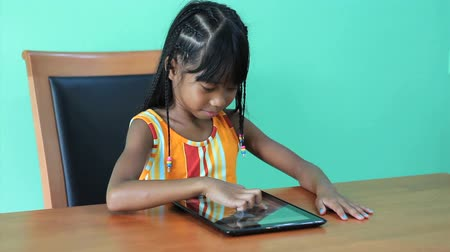 touchpad : A cute seven year old Asian girl is excited to use her new digital tablet. Stock Footage