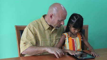 touchpad : A cute little 7 year old girl has fun playing on her dads digital tablet.